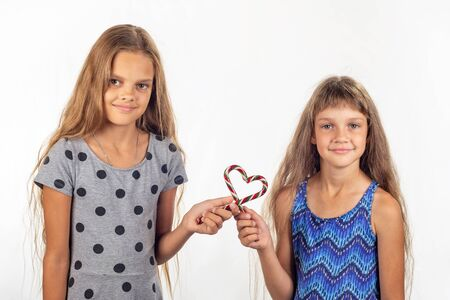 Two girls made a heart out of two lollipops and look into the frame