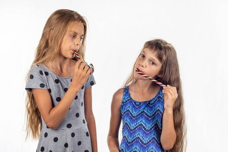 Twee meisjes zuigen karamelsnoepjes