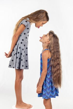 A girl stands on a chair, another girl stands nearby, show each other tongues
