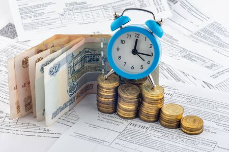 Hours, paper rubles, stacks of coins, receipt with accrued interest on electricity
