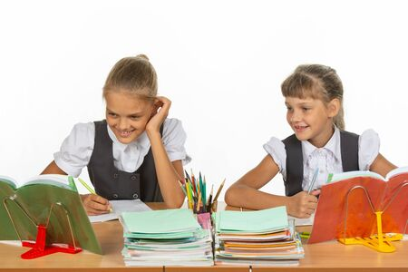 Two schoolgirls are sitting at a desk and cheerfully looking at the textbook