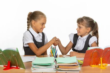 Two girls at a desk shake hands