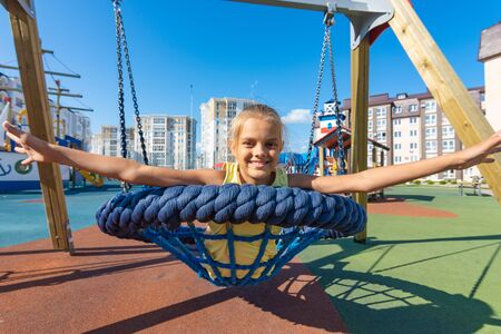 Girl joyfully spread her arms while riding on a round hanging swing