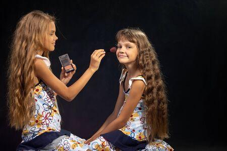 De oudere zus brengt poeder aan op het gezicht van het jongere meisje