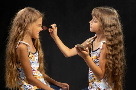 Girl powdering with a brush a nose to another girl, studio, black background