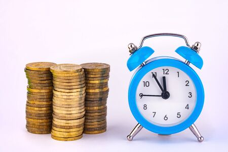 Clock and stacks of coins are close by, close-up Stock Photo - 129831828
