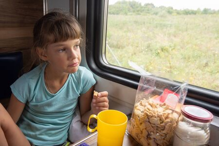The girl eats cookies on the train and looks out the window Imagens - 129832691