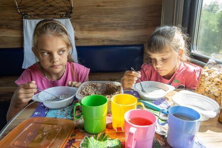 Two girls eat buckwheat with milk from plastic disposable tableware on a train