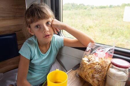 Girl sitting in a reserved seat carriage in a train funny looks in the frame Imagens