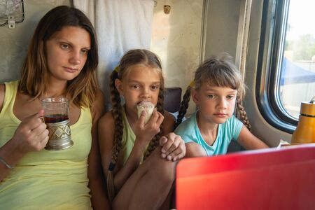 Mom and two girls are looking at the laptop screen in the train car, having a bite while Stock Photo