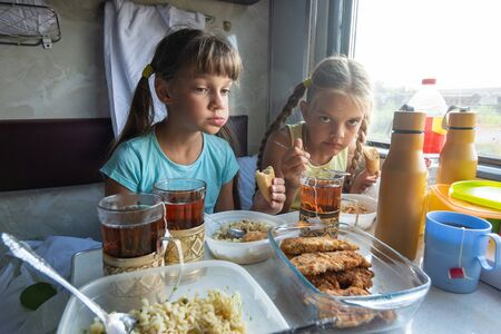 Two girls have lunch in the reserved seat of the train