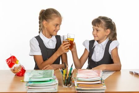 Two funny schoolgirls at a table drink juice, and banged glasses