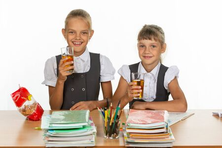 Two funny schoolgirls at a table drink juice, and look in the frame Imagens