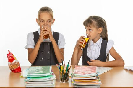 Two school friends drink juice at a table in a school class