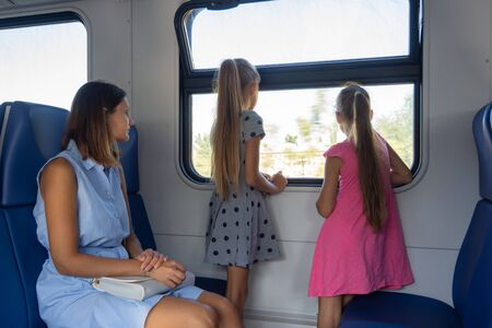 Mom and two daughters ride in an electric train, children standing looking out the window
