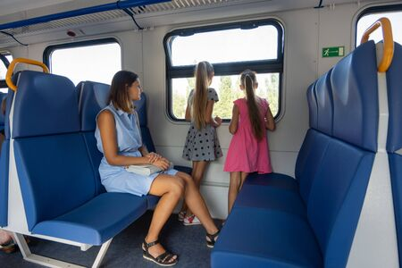 Mom and two daughters ride in an electric train, a general view of the seats Stok Fotoğraf