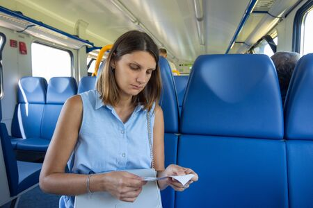 A girl in an electric train looks at a ticket