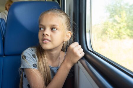 Girl sitting by the window in an electric train car Stok Fotoğraf