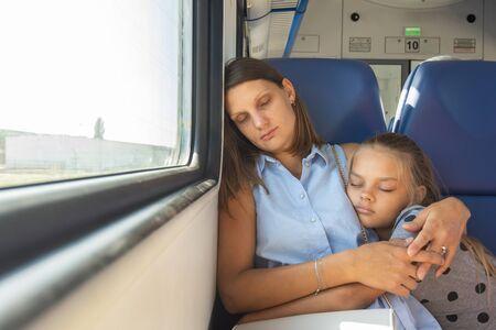 Mom and daughter hugging sleeping in a train car Reklamní fotografie