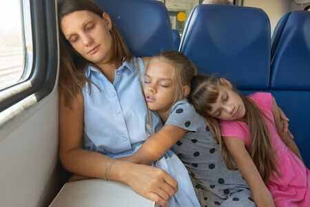 Mom and two daughters fell asleep in an electric train car Reklamní fotografie