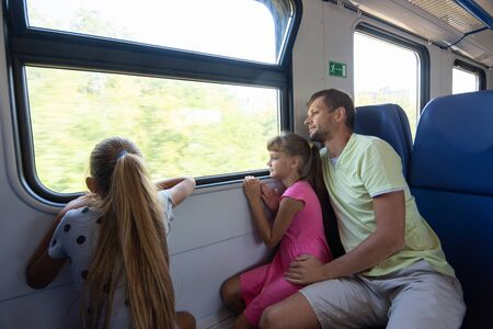 Dad and two daughters in an electric train car, look out the window with enthusiasm Stok Fotoğraf