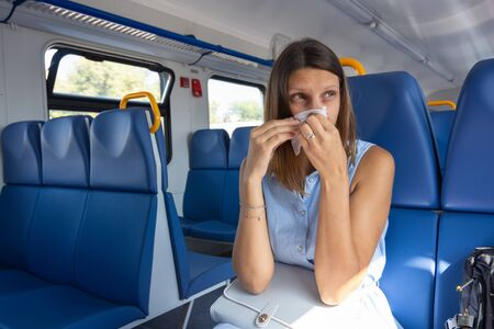 A cold girl blows her nose in a scarf in an electric train car