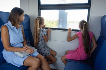 Mom and two daughters ride in an electric train, children look out the window Stok Fotoğraf