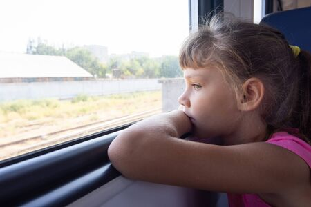 A girl of eight years looks out the window in an electric train