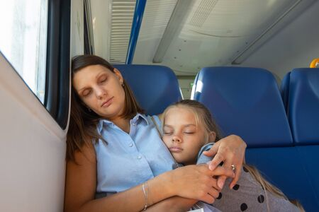 Mom and daughter sleep in a seated carriage of an electric train