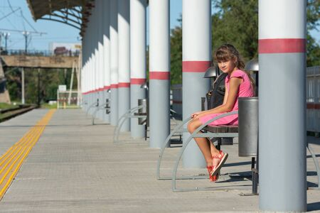 Eight-year-old girl sits alone on the empty platform of the train station