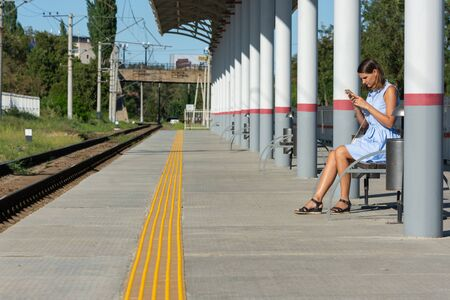 Young girl with a phone waits for a train on the empty platform of the railway station Reklamní fotografie