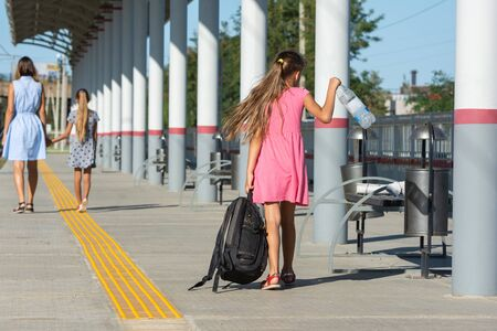 The girl and daughter are walking along the platform of the railway station, another girl with a large backpack is trying to catch up with them