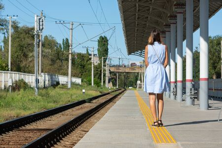 Young beautiful girl stands alone on a railway platform with her back to the camera