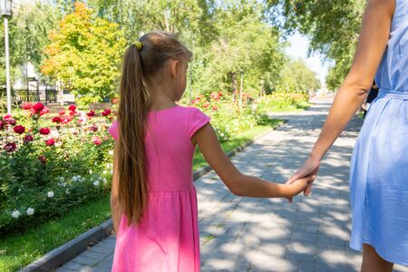 A girl walks along the alley and holds moms hand