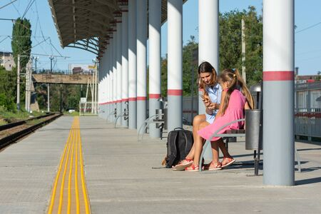 Mom and daughters are waiting for the train on the empty platform of the railway station Reklamní fotografie