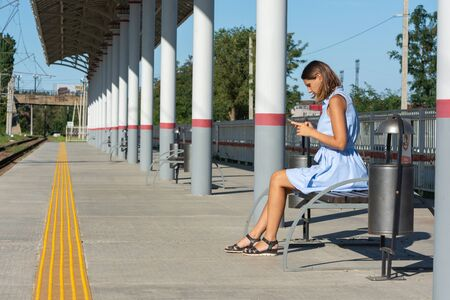 Young girl looks at the phone on the empty platform of the railway station Reklamní fotografie