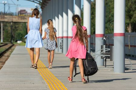 A girl and a daughter walk along the platform of the railway station, another girl with a large backpack catches up with them