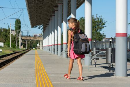 Eight-year-old girl walks on the empty platform of the railway station