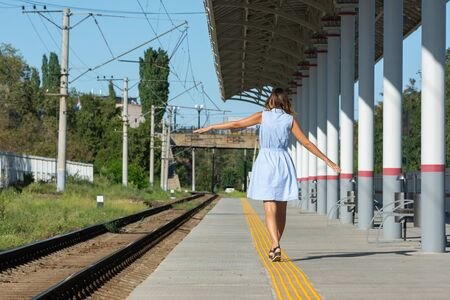 Young beautiful girl goes on the platform holding her arms outstretched to the side Reklamní fotografie
