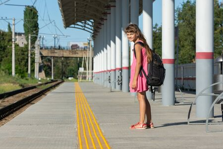 The eight-year-old girl on the platform of the railway station turned around and looked into the frame