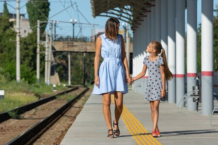 Young beautiful girl and teenage daughter walk on the empty platform of the train station