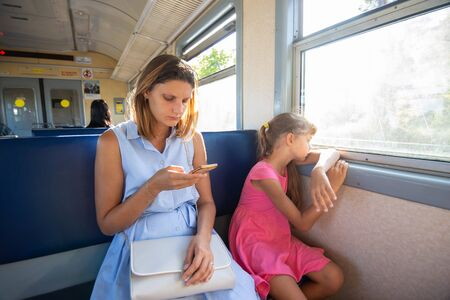 A young girl looks at the phone, daughter at the window in the electric train Reklamní fotografie