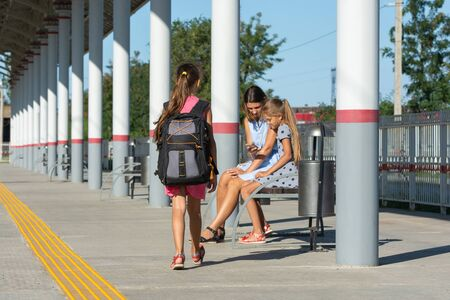 A girl with a large backpack approaches a girl with a daughter sitting on a bench on the platform of the railway station