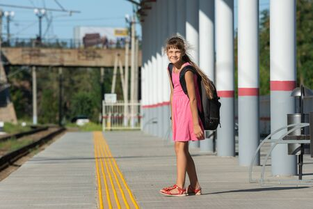 The eight-year-old girl on the platform of the train station looked funny in the frame