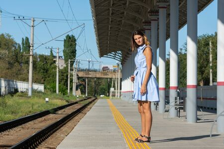 Young beautiful girl stands alone on a railway platform and looks into the distance with anticipation