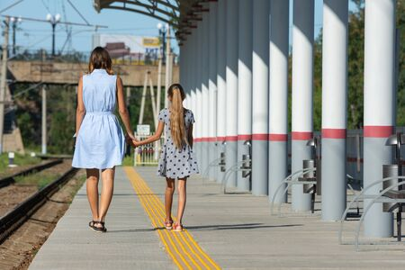 Young beautiful girl and teenage daughter walk from the camera on the empty platform of the train station Reklamní fotografie
