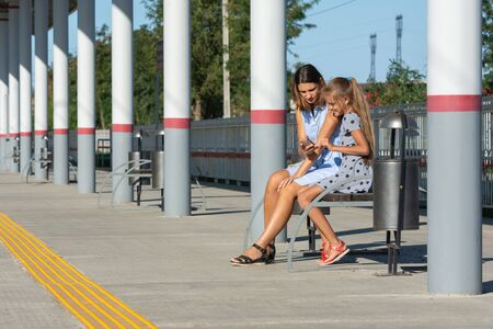 Mom and daughters wait for the train and look at the phone on the empty platform of the railway station Reklamní fotografie