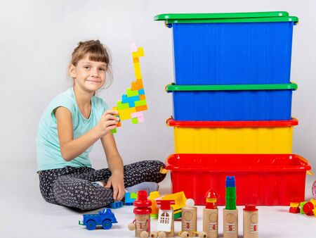 Girl playing toys, large plastic boxes are standing nearby