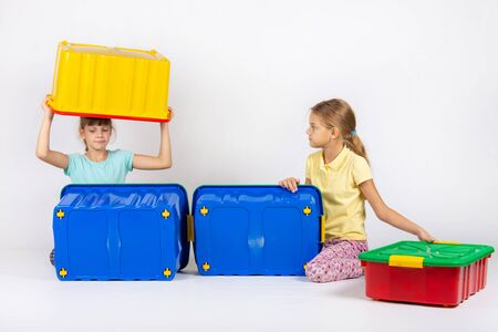 Two girls play with large plastic boxes Reklamní fotografie
