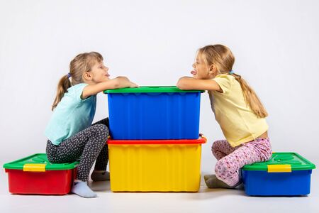 Two girls sit on big boxes for toys and show each other tongue